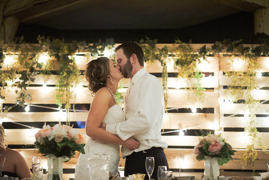 bride and groom kissing in front of backdrop with string lights