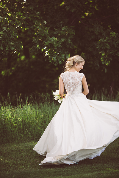 bride twirling in her bridal gown - back