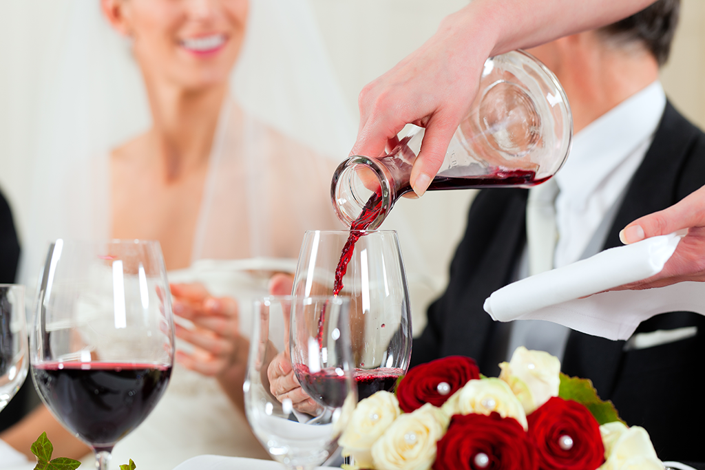 red wine being poured at wedding