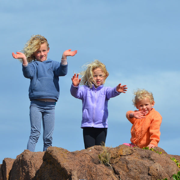 3 kids standing on a rock