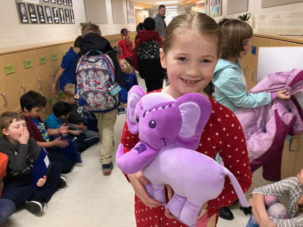 Girl holding Generation Mindful's Violet Elephant SnuggleBuddies