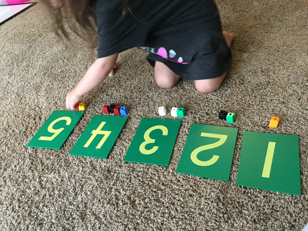 Young girl matching blocks to numbered cards for play-based learning
