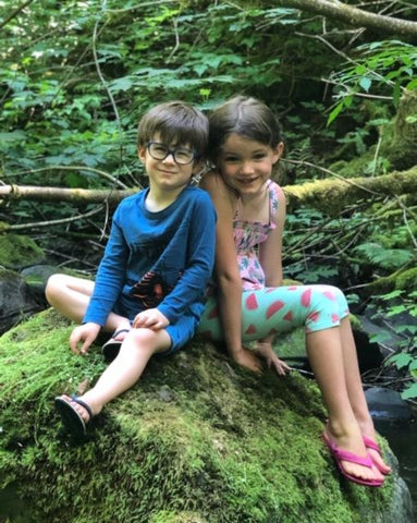 two children sitting together in nature
