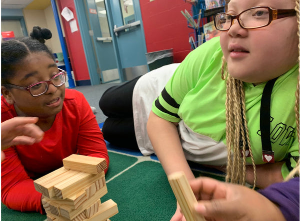 "Sierra and a peer participate in ""Yoga Jenga,"" an activity that facilitates social-emotional inclusive practices and mind-body awareness."