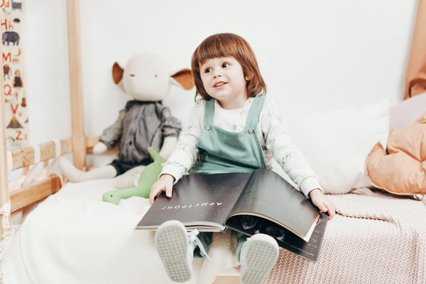 Child sitting on the bed reading a book