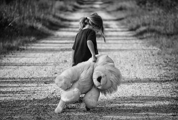 girl carrying a large stuffed lion down a dirt road