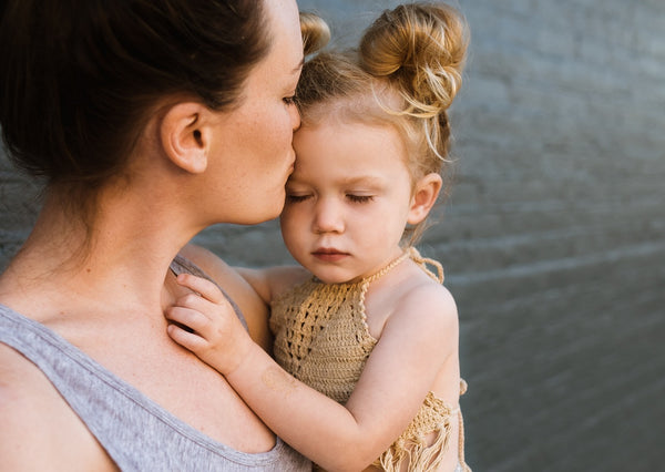 how to discipline a toddler while being supportive: mother kissing daughter