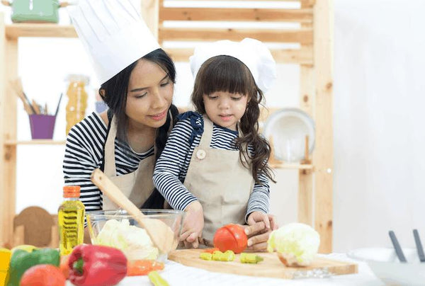 mom teaching her daughter to cook