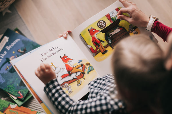 Child reading a book about a fox
