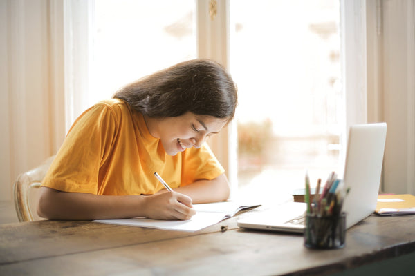 A girl in a yellow shirt doing school work at home