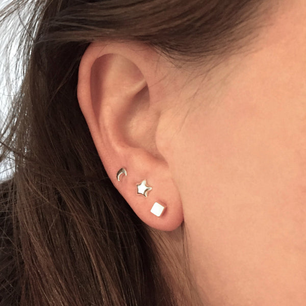 Layer up with tiny studs - model is wearing Moon, Star and a cube stud from Brash Bijoux.