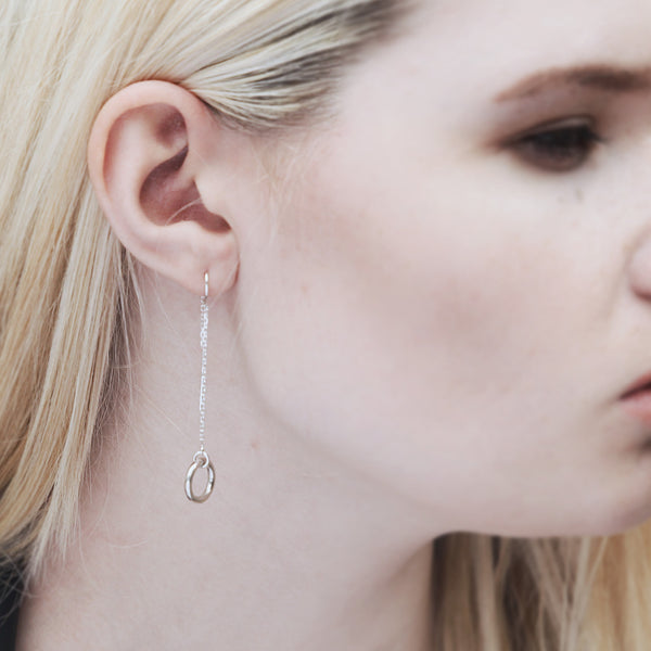 Sterling silver dangle earrings as worn on a model, Thread earrings with a solid ring.