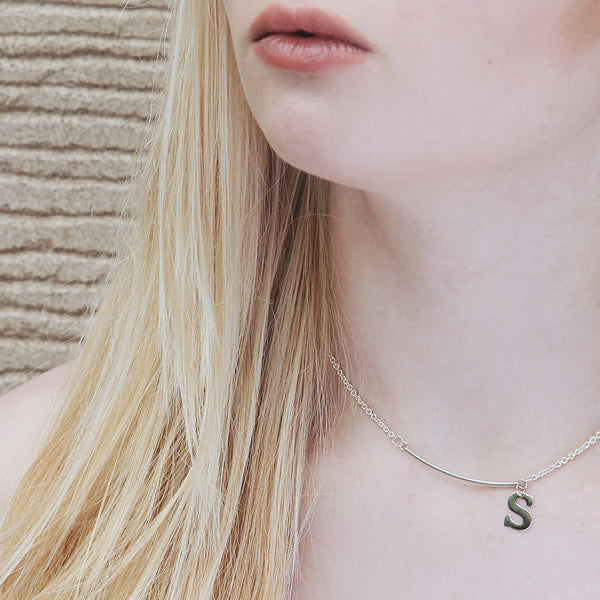 Personalised sterling silver necklace, hand-cut initial of your choice is attached to a solid curved bar. Picture shown with necklace on model
