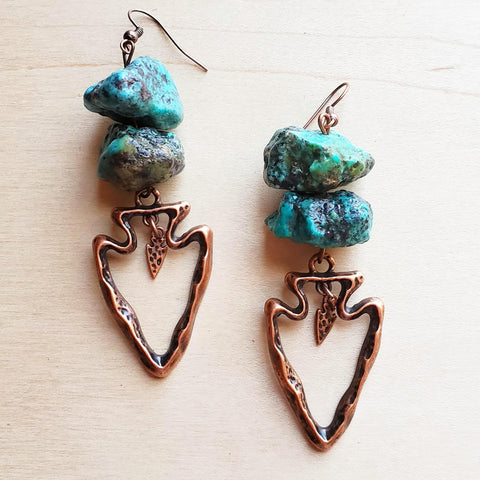 A pair of handmade turquoise dangle earrings with a copper arrowhead from The Jewelry Junkie.