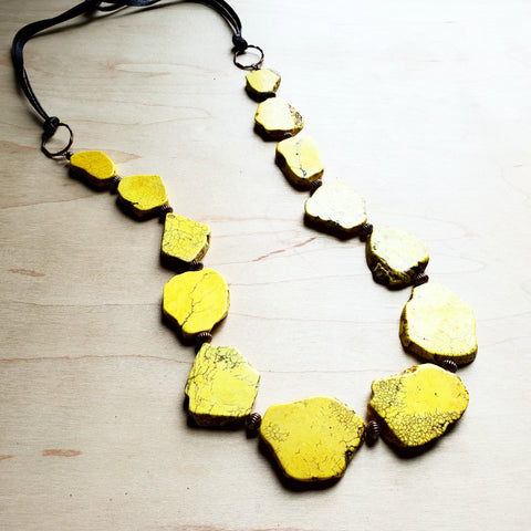 A yellow turquoise stone necklace with leather ties from The Jewelry Junkie.