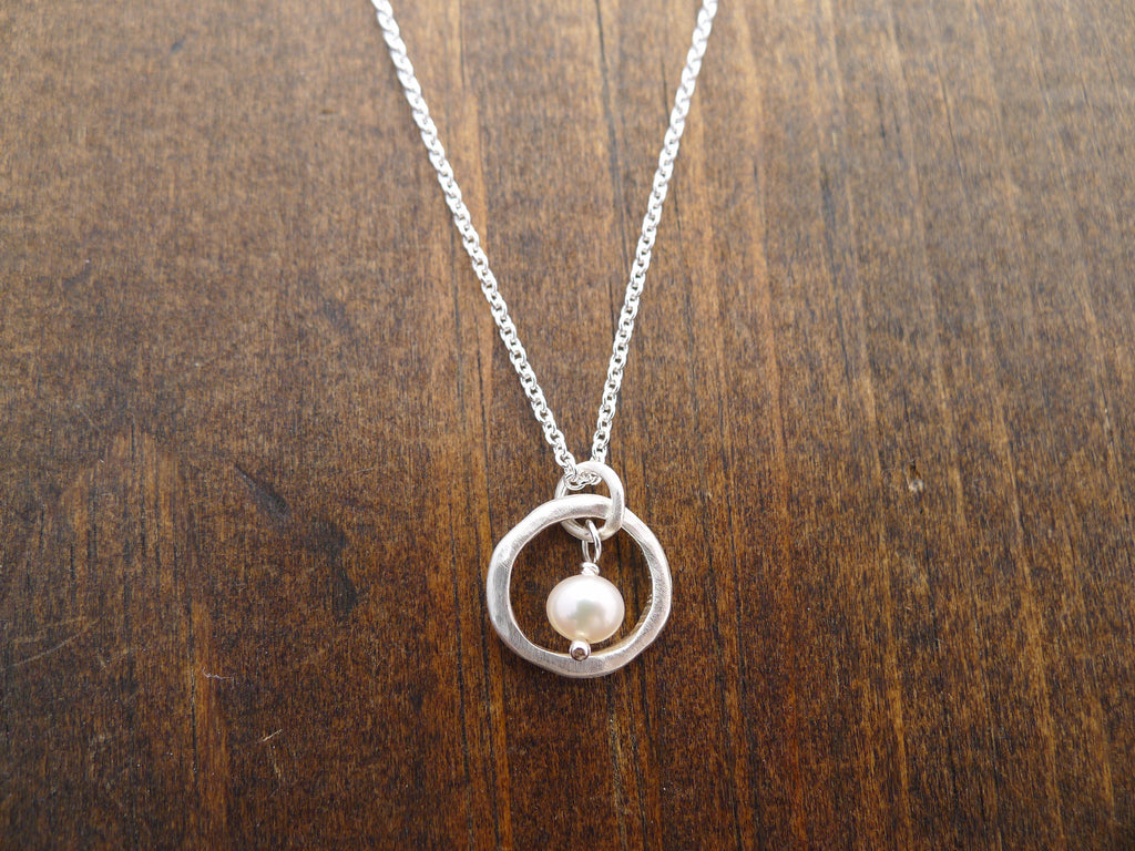 silver circle with pearl necklace