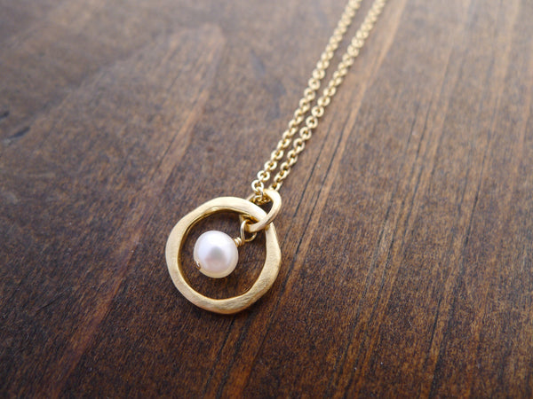 gold circle with pearl necklace