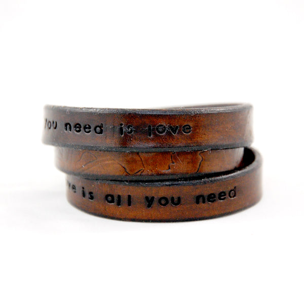 Triple wrap leather bracelet stamped with repeating All you Need is Love, Love is all you need