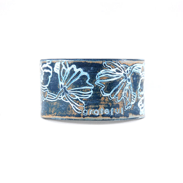 Embossed leather cuff bracelet stamped with the word Grateful finished in blue and white