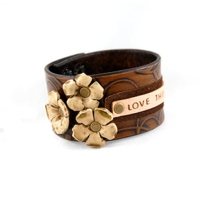 Handmade leather cuff bracelet with a 3 hand sculpted leather flowers stamped with the phrase Love This Life