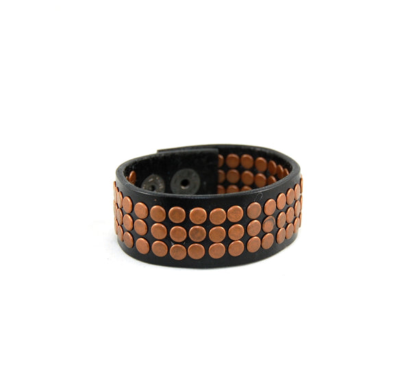 The rocker 78 handmade leather cuff with 78 handset metal rivets black with copper rivets
