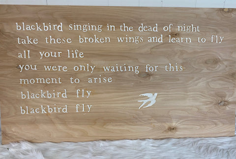 Wood sign with words and bird castings