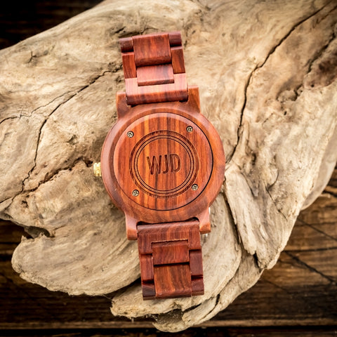 engraved red sandalwood wood watch laying on a rock