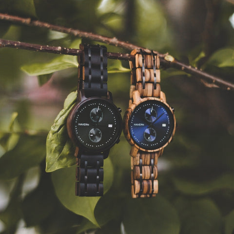 two wooden watches hanging from a tree branch