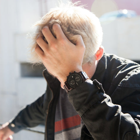 man touching his head with a ebony watch on his wrist