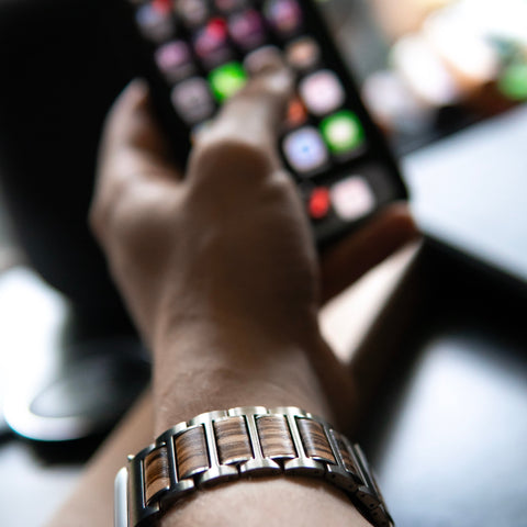 apple watch band on mens wrist holding phone