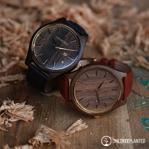 two leather band wooden watches laying on a whiskey barrel top