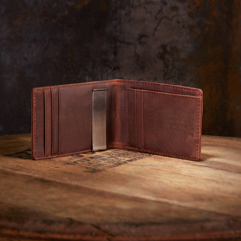 engraved leather wallet on wooden whiskey barrel