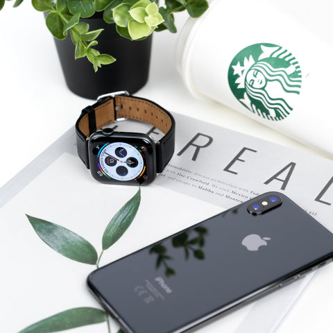 world clock watch and phone lying on book next to coffee and plant