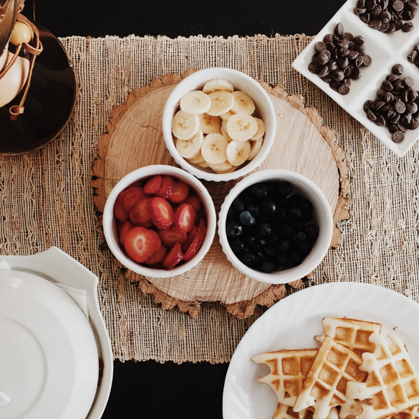 Waffles with Waffle Toppings Laid Out on Kitchen Table