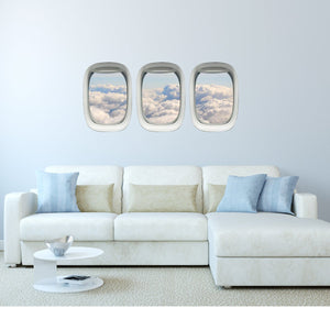 Pack of three airplane windows with view of clouds