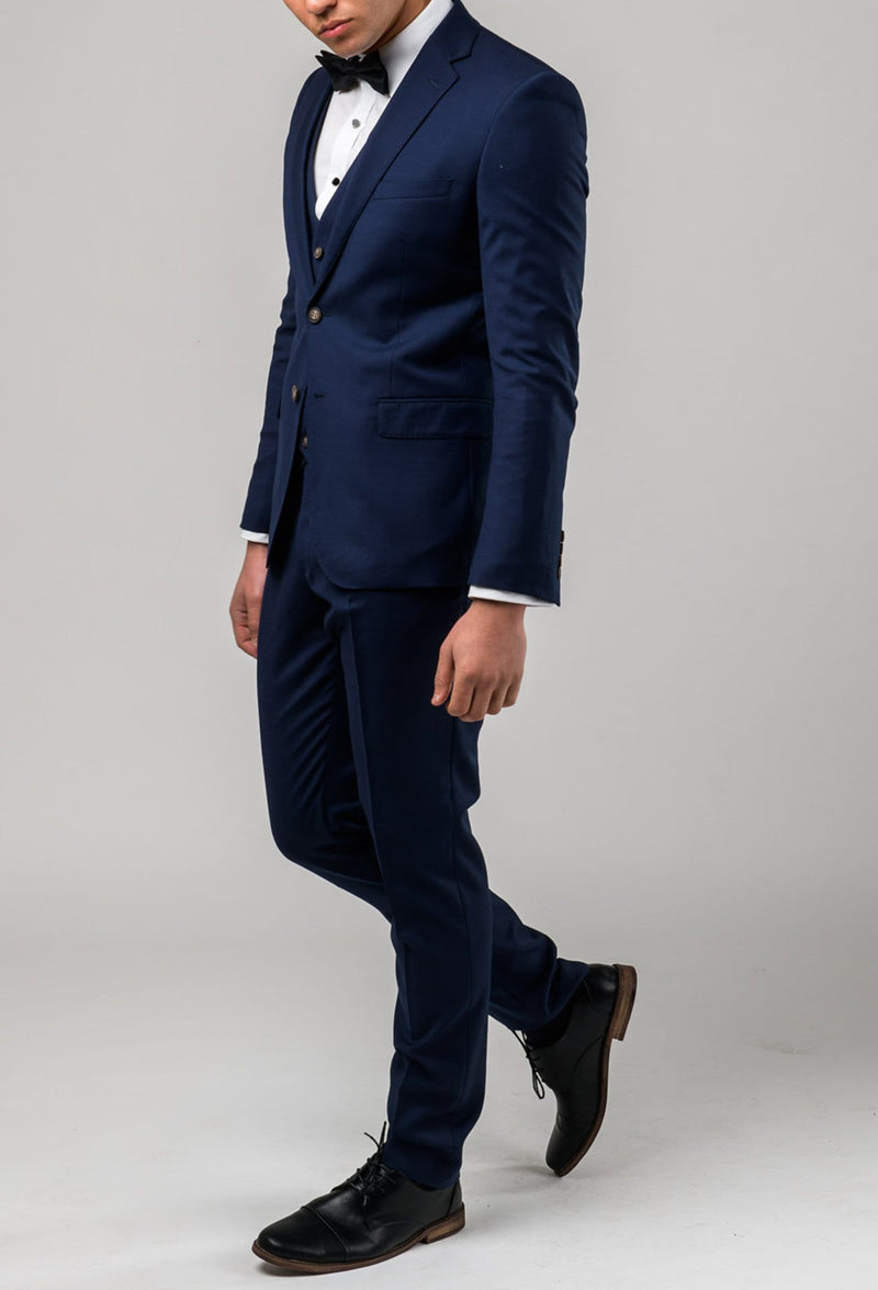 a side on view of the Aston slim fit colton suit in royal blue pure wool A0521512S styled with a white shirt and black bow tie