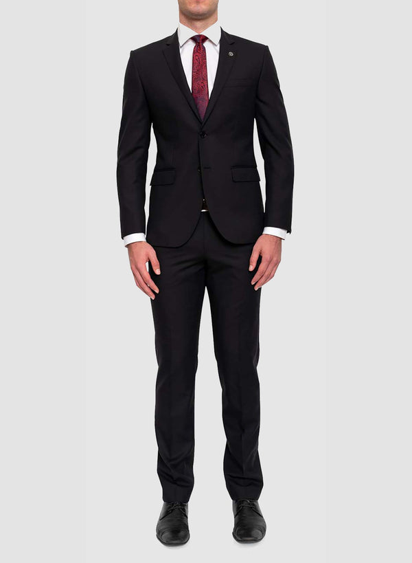 A model faces the camera wearing the Cambridge classic fit range suit in black pure wool F225 styled with a white shirt and a red tie