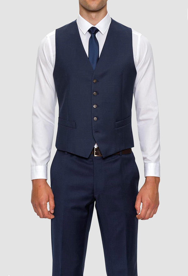 A front on view of a model wearing A model wears the Gibson slim fit mighty vest in navy pure wool with a white shirt and navy tie