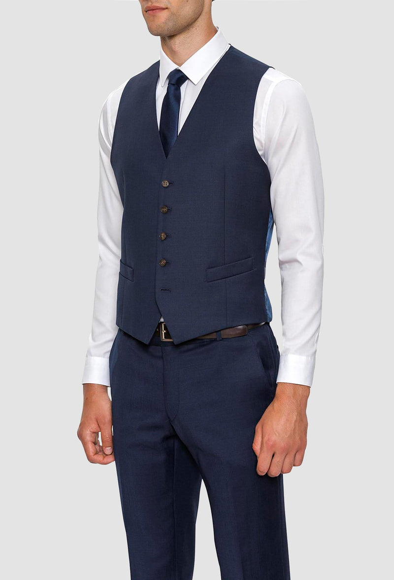 A model wears the Gibson slim fit mighty vest in navy pure wool with a white shirt and navy tie