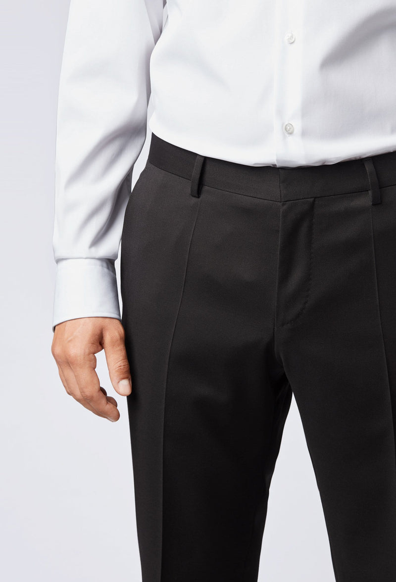 A close up view of the front of a black trouser detail in the Hugo Boss classic fit johnstons suit in black styled with a white shirt