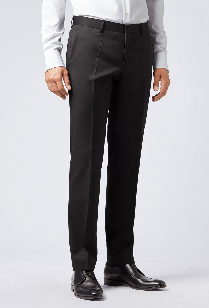 A side view of a man wearing the Hugo Boss classic fit johnstons suit trouser in black