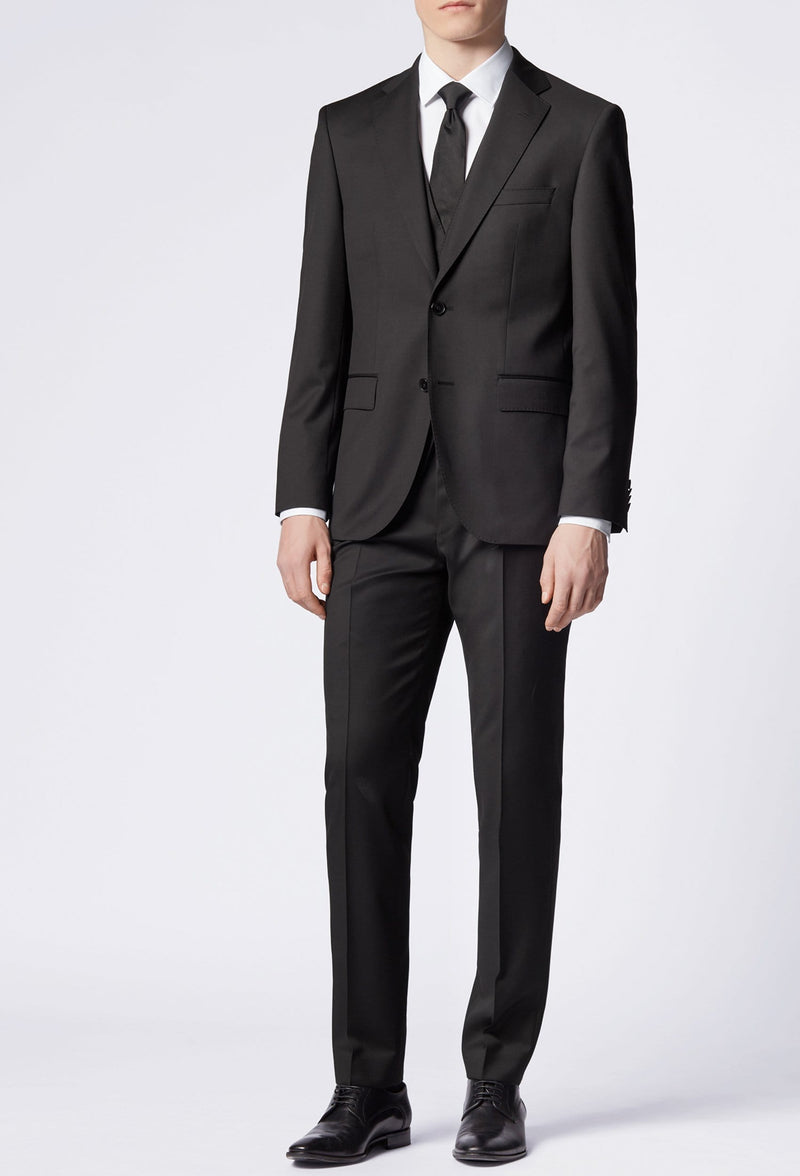 A front view of a slim man standing in the Hugo Boss classic fit johnstons suit in black pure wool, styled with a white shirt and a black tie