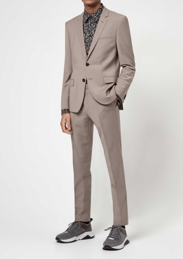 a model wears the Hugo slim fit arti hesten suit in medium beige pure wool with grey sneakers and a black printed shirt