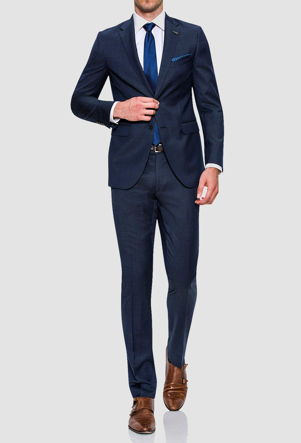 a man wears the joe black mission suit in a textured navy wool  showing the full length style