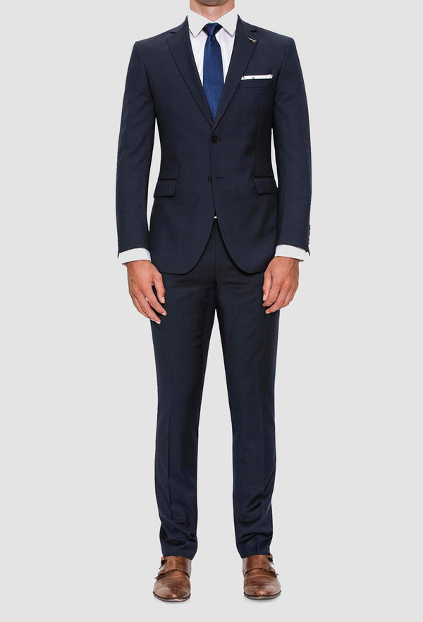 A full length view of the Joe Black slim fit anchor suit in navy pure wool FJV033 styled with a white shirt and a blue tie on a grey background