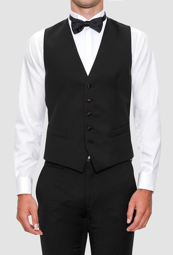 a model wears the Joe Black slim fit mail vest in black pure wool styled with a white shirt and black bow tie