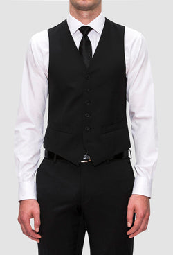 a front view of a model wearing the Joe Black slim fit mail vest in black pure wool with a white shirt and a black tie
