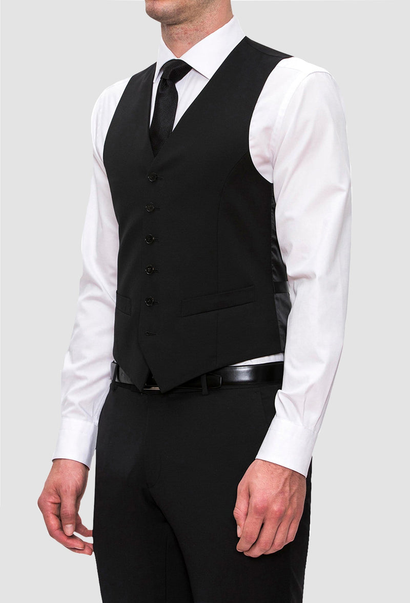 a side on view of a model wearing the Joe Black slim fit mail vest in black pure wool with a white shirt underneath and a black tie