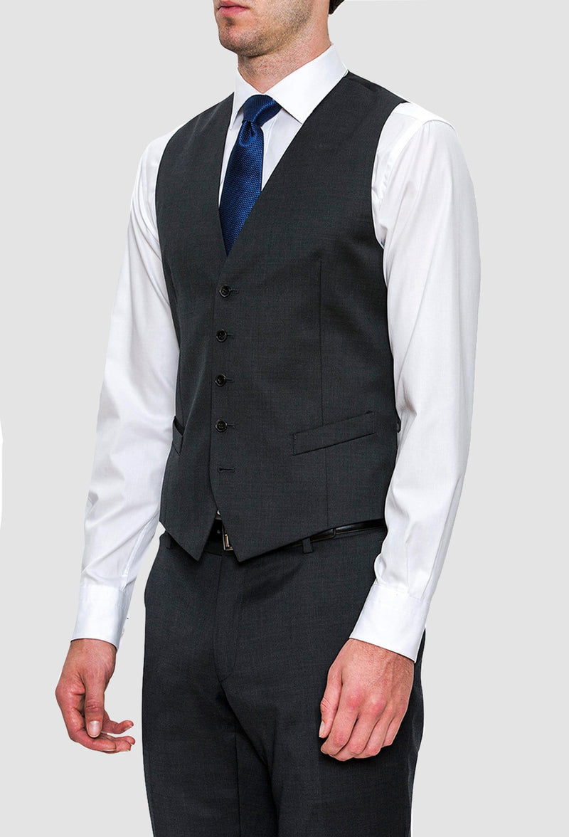 a side view of a model wearing the Joe Black slim fit mail vest in charcoal pure wool FCZ027 layered over a white shirt with a blue tie