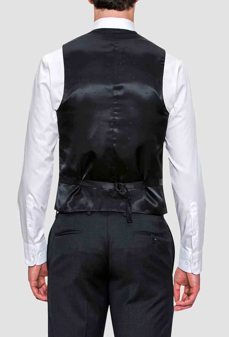 the back view of the Joe Black slim fit mail vest in charcoal pure wool layered over a navy trouser and white shirt